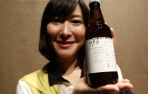 """A Kirin staff member poses with its new craft beer product """"Spring Valley Brewery 496 prototype,"""" which was launched in July 2014. Craft styles are increasingly migrating from the United States to other countries."""