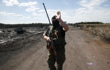 An armed pro-Russian separatist gestures to reporters at the crash site of Malaysia Airlines Flight MH17, near the village of Hrabove (Grabovo), Donetsk region July 21, 2014.