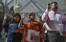 New American citizens (L to R) Leslie Tapia, from Mexico, Sanzida Khanam, from Bangladesh and Pablo Espinales, from Ecuador, raise their hands for the Pledge of Allegiance during a naturalization ceremony at The Metropolitan Museum of Art in New York on J