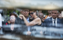 Family members of the victims killed in Malaysia Airlines Flight MH17 plane disaster are seen through the window of a hearse carrying the victims' bodies.