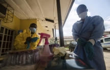 Medical staff put on protective gear in the Kenema government hospital before taking a sample from a suspected Ebola patient in Kenema, Sierra Leone.