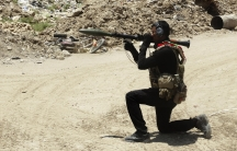 A member of the Iraqi Special Operations Forces (ISOF) takes his position during a patrol looking for militants of the Islamic State, formerly known as the Islamic State of Iraq and the Levant (ISIL), in a neighborhood in Ramadi, July 23, 2014.