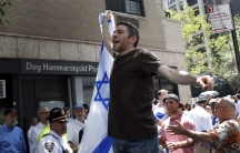 A man holds up an Israeli flag during a pro-Israel demonstration near the United Nations building in New York City, July 28, 2014.