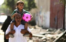 A Palestinian carries his son in the eastern Gaza City neighborhood of Shejaiya, which witnesses said was heavily hit by Israeli shelling and air strikes during an Israeli offensive. (August 1, 2014)