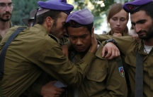 Israeli soldiers mourn during the funeral of their comrade Lieutenant Hadar Goldin in Kfar Saba, near Tel Aviv, on August 3, 2014. Goldin's death in Gaza is prompting some in Israel to question their military's controversial Hannibal Doctrine.