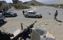Afghan National Army soldiers inspect a car at a checkpoint near the British-run military training academy, Camp Qargha, in Kabul on August 6, 2014.