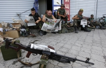 Ukrainian servicemen read newspapers as they rest at a checkpoint near the eastern Ukrainian town of Debaltseve in the Donetsk Region on August 6, 2014.