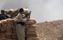 Kurdish peshmerga troops stand guard in the Iraqi province of Nineveh on August 6, 2014.