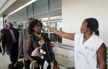 A health worker takes a passenger's temperature with an infrared digital laser thermometer at Abidjan's Felix Houphouet Boigny International Airport in Cote d'Ivoire.