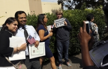 A man holds a voter registration sign while a couple has a souvenir photograph taken following a US Citizenship and Immigration Services ceremony in Oakland, Californiam on August 13, 2014.