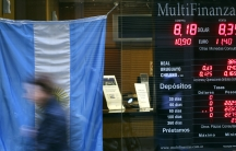 A woman walks past a currency exchange store with an Argentine national flag on display in Buenos Aires' financial district on August 14, 2014