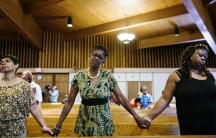 Parishioners hold hands during church services at the Greater St. Mark Family Church as the community discusses reactions to the shooting of teenager Michael Brown in Ferguson, Mo., on August 17, 2014.