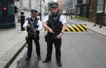 Armed police officers pose for the media on Downing Street, in central London, on August 29, 2014.