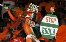 A fan of Ivory coast holds a sign with a message against Ebola during the 2015 African Nations Cup qualifying soccer match between Ivory Coast and Sierra Leone.
