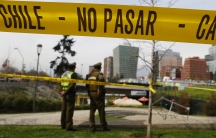 """Police officers are seen behind barricade tape guarding an area where a bomb exploded in Santiago September 8, 2014. The words on the yellow tape read, """"Do not pass."""""""