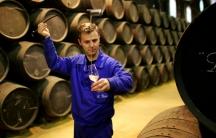 """A worker pours manzanilla wine into a wine taster from a oak barrel in the wine cellar """"La Guita"""" in Sanlucar de Barrameda, southern Spain"""