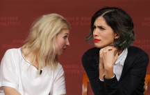 Maria Alyokhina (L) and Nadezhda Tolokonnikova, members of the punk collective Pussy Riot, listen to a question from the audience during a forum at Harvard's Kennedy School of Government, a few days before they made an appearance in Ann Arbor, MI.