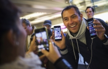 Michele Mattana of Sardinia, Italy, poses with an iPhone 6 Plus and an iPhone 6 on the first day of sales at the Fifth Avenue store in Manhattan on September 19, 2014.