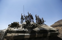 Shiite Houthi rebels gesture as they stand atop an army vehicle they took from the compound of the army's First Armoured Division in Sanaa on September 22, 2014.