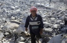 A man inspects a damaged site in what activists say was a US strike in Kfredrian, Idlib province, Syria, on September 23, 2014.