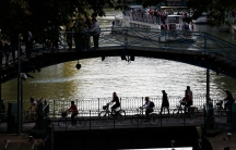 People ride bicycles across the Canal Saint-Martin in Paris, the city's main canal.