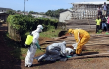 Health workers remove the body a woman who died from the Ebola virus in the Aberdeen district of Freetown, Sierra Leone, on October 14, 2014.