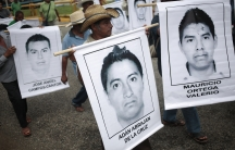 People carry photographs of missing students during a march in Acapulco on October 17, 2014. On September 26, police allegedly linked to a criminal gang shot dead at least three students and abducted dozens of others during clashes in the southwestern cit