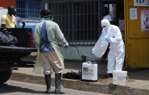 A member of a burial team prepares to spray a colleague with chlorine disinfectant in Monrovia.
