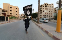 A member loyal to the ISIS waves the ISIS flag in Raqqa
