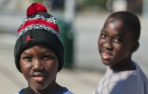 """Young residents pose for a photograph on a street in the Clifton neighborhood of Staten Island in New York on October 25, 2014. The area is home to a community known as """"Little Liberia"""" — it has the largest concentration of Liberians outside of Africa."""