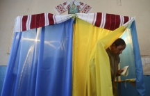 A man walks out of a voting booth at a polling station during a parliamentary election in the village of Fiina near Lviv, on October 26, 2014.