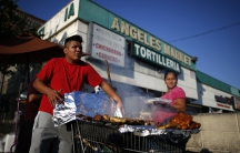 A man cooks meat in a shopping cart in the Westlake area of Los Angeles, home to many Mexican and Central American migrants, California August 6, 2014.