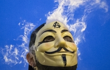 """A man in a Guy Fawkes mask smokes while joining supporters of the Anonymous movement taking part in the global """"Million Mask March"""" protests in New York, on November 5, 2014."""