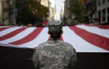 U.S. Army soldiers carry a large U.S. flag as they march in the Veterans Day parade on 5th Avenue in New York November 11, 2014.