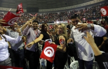 Supporters of Beji Caid Essebsi, the Nidaa Tounes party leader and presidential candidate, wave flags and shout slogans during a presidential electoral campaign rally in Tunis on November 15, 2014.