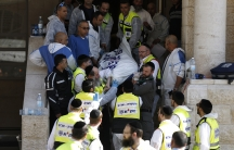 Israeli emergency personnel carry the body of a victim from the scene of an attack at a Jerusalem synagogue on November 18, 2014.