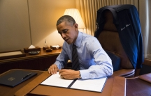 President Barack Obama signs two Presidential Memoranda associated with his Executive Actions on immigration aboard Air Force One on November 21, 2014.