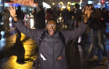 A protester shouts with both his hands in the air while marching through a suburb of St. Louis, Missouri, on November 23, 2014.