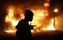 A man walks past a burning building during rioting after a grand jury returned no indictment in the shooting of Michael Brown in Ferguson, Missouri.
