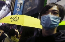 A pro-democracy protester carries a yellow umbrella, symbol of the Occupy Central civil disobedience movement, while gathering with other protesters at Mong Kok shopping district in Hong Kong on November 27, 2014.