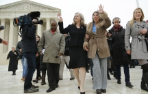 Peggy Young (3rd R) and her attorney Sharon Gustafson (4th R) wave to supporters as they depart the US Supreme Court building on December 3, 2014.
