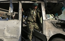 An Afghan soldier inspects the site of a suicide attack in Kabul on December 11, 2014. A suicide bomber targeted a bus carrying Afghan army personnel, killing six soldiers and wounding 11.
