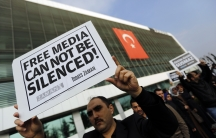 Journalists of Turkey's Zaman daily newspaper in Istanbul protest a police raid of the media outlet. 24 people including top executives and ex-police officers were round up in what Turkish president Tayyip Erdogan calls a terrorist network conspiring to t