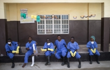 Health workers rest outside a quarantine zone at a Red Cross facility in the town of Koidu, Kono district in Eastern Sierra Leone December 19, 2014. Sierra Leone, neighbouring Guinea and Liberia was at the heart of the world's worst recorded outbreak of E