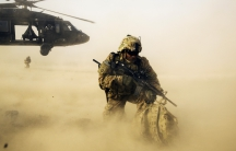A U.S. soldier from the 3rd Cavalry Regiment shields himself from the rotor wash of a UH-60 Blackhawk helicopter after being dropped off for a mission with the Afghan police near Jalalabad in the Nangarhar province of Afghanistan December 20, 2014.