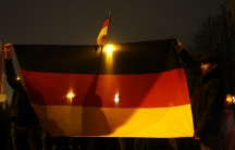 Participants in a grassroots anti-Muslim movement hold German flags during a demonstration in Berlin. The rise of the group, Patriotic Europeans Against the Islamisation of the West, has shaken Germany's political establishment.