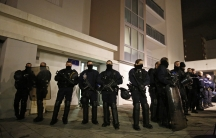 Police officers secure access to a residential building during investigations in the eastern French city of Reims on January 8, 2015, after the shooting against the Paris offices of Charlie Hebdo, a satirical newspaper.
