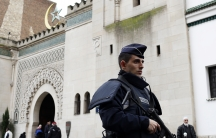 A French policeman stands in front of the entrance of Paris Mosque as French Muslims gather for Friday prayers in Paris January 9, 2015, following Wednesday's deadly attack at the Paris offices of weekly satirical newspaper Charlie Hebdo by two masked gun