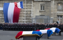 French police officers pay respects at a national tribute in Paris to the three officers who fell during last week's attacks by Islamic militants.