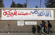 "People walk past a graffiti reading ""Al Qaeda is American-made"""